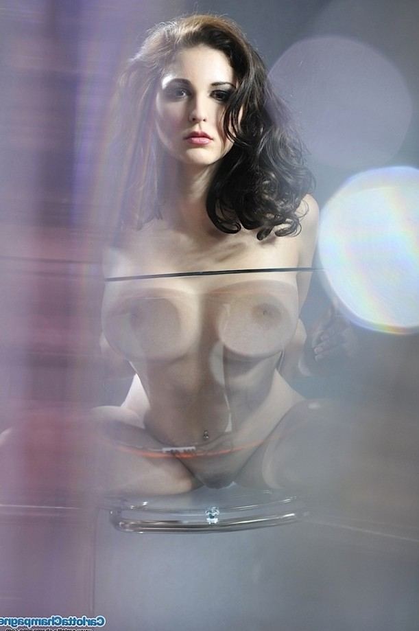 Carlotta Champagne presses her boobs on the glass.